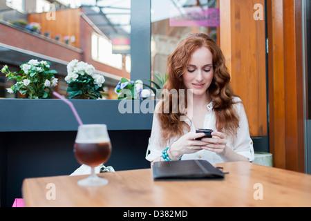 Holland, Goirle, elegante Dame im Café mit Handy - Stockfoto