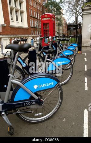 Fahrräder für London Cycle Hire Regelung säumen die Strasse vor eine ikonische rote Telefonzelle - Stockfoto