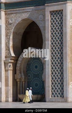 Marokkanische Männer tragen Jalabiyas vorbei an eines der Tore der Hassan II Moschee in Casablanca, Marokko - Stockfoto
