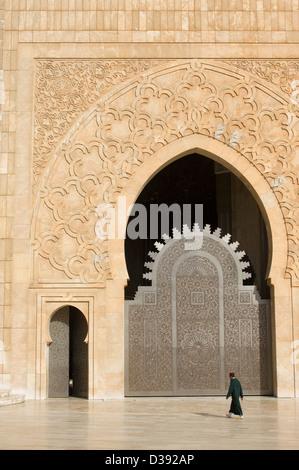 Mann trägt einen Fez, vorbei an einer der Türen der Hassan II Moschee in Casablanca, Marokko - Stockfoto