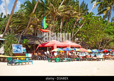 Die Touristen liegen unter Sonnenschirmen am Strand von Mirissa, südlichen Sri Lanka außerhalb der Wadiya Magical - Stockfoto
