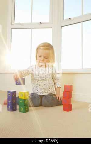 Mädchen spielen mit Klötzchen auf Etage - Stockfoto