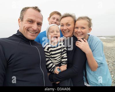 Familie gemeinsam lachen auf felsigen Strand - Stockfoto