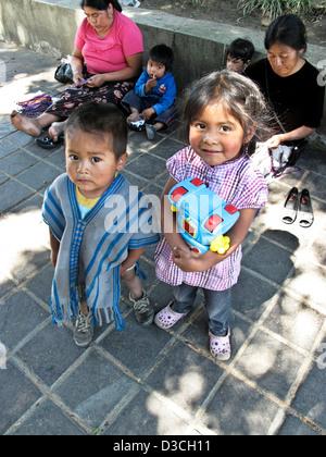 schöne kleine mexikanischen indigenen Indianerjunge mit etwas älteren Schwester hält Plastikspielzeug in Oaxaca - Stockfoto