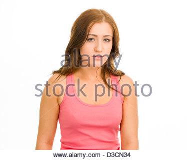 Junge Frau in einem rosa Tanktop auf weißem Hintergrund. Sie hat einen ernsten Blick. - Stockfoto