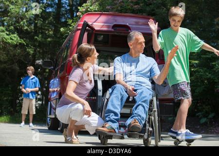 Menschen mit Querschnittlähmung im Rollstuhl geben High-Five Sohn auf skateboard - Stockfoto