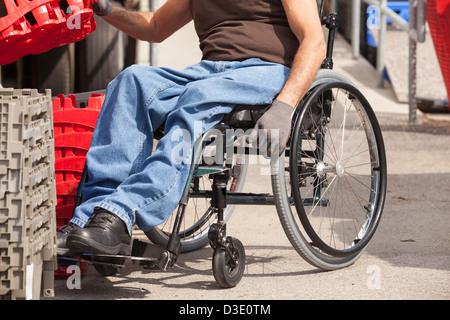 Laden Hafenarbeiter mit Querschnittslähmung im Rollstuhl Stapeln Inventar Tabletts - Stockfoto