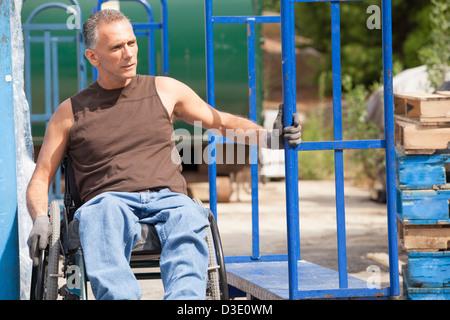 Laden Hafenarbeiter mit Querschnittslähmung im Rollstuhl bewegen einen Hand-LKW - Stockfoto