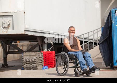 Laden Hafenarbeiter mit Querschnittslähmung im Rollstuhl im Lagerbereich - Stockfoto
