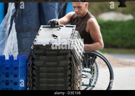Laden Hafenarbeiter mit Querschnittslähmung im Rollstuhl bewegen gestapelt Inventar Tabletts - Stockfoto