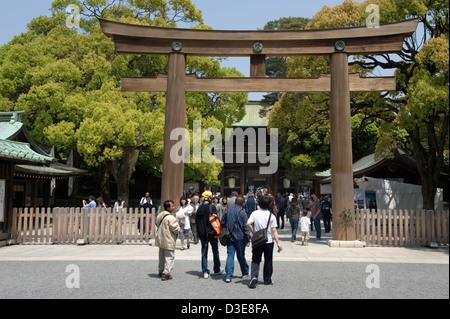 Besucher nähert sich die Zypresse aus Holz Torii Tor vor dem Haupteingang am Meiji Jingu kaiserliche Schrein in - Stockfoto