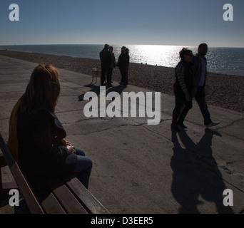 Silhouette über der Schulter einer einzigen Frau sitzt auf einem Sitz, Leute vorbeigehen und unterhielt sich mit - Stockfoto