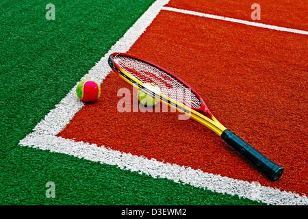 Farbige Tennisbälle und Tennisschläger, in der Ecke eines synthetischen Feldes platziert. - Stockfoto