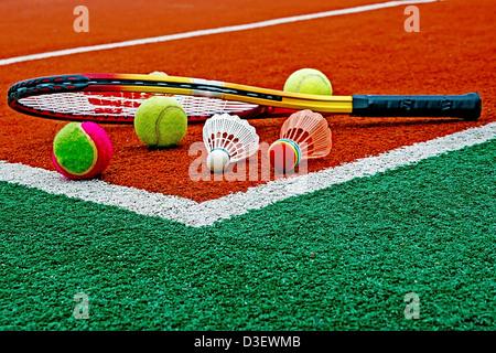 Badminton Federbälle mit Tennisbälle und Tennisschläger, gefärbt in der Ecke eines synthetischen Feldes platziert. - Stockfoto