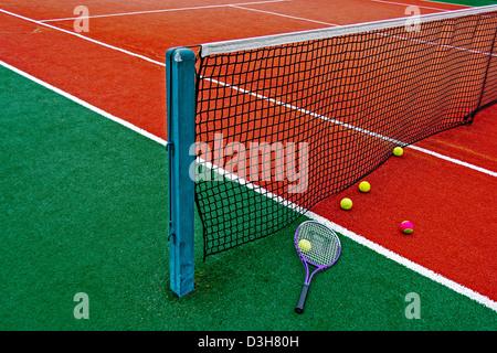 Ball und Tennis Schläger um das Netz auf einem synthetischen Feld angeordnet. - Stockfoto