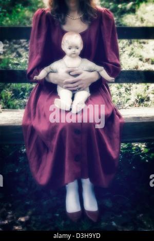 eine Frau in einem roten Kleid sitzt auf einer Holzbank mit einer alten Puppe auf dem Schoß - Stockfoto