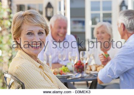 Porträt von lächelnden senior Frau auf der Terrasse mit Freunden genießen, Wein und Mittagessen im Hintergrund - Stockfoto