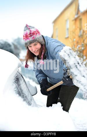 Eine Autofahrer löscht Schnee aus ihrem Auto in das Dorf von Badminton Gloucestershire UK - Stockfoto