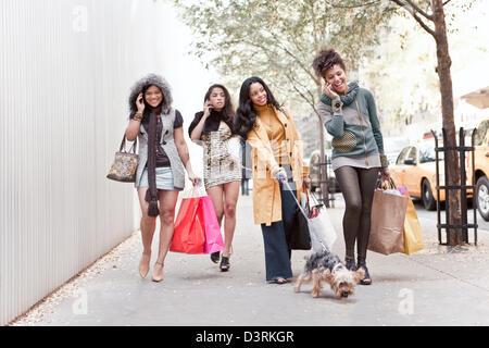 Gruppe von Freundinnen reden über Handy während des Gehens - Stockfoto