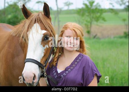 Lächelndes Mädchen mit ihrem Pferd in Freizeitkleidung Porträt des roten Haaren Teenager und ihr Tier. - Stockfoto