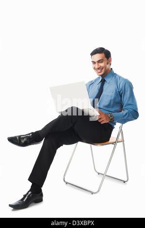 Bengali Geschäftsmann mit einem Laptop auf einem Stuhl - Stockfoto