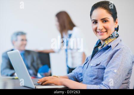 Porträt von eine Geschäftsfrau, die mit ihren Kollegen im Hintergrund auf einem Laptop arbeiten - Stockfoto