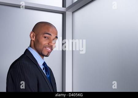 Porträt eines lächelnden gutaussehenden Geschäftsmann neben einem Büro-Fenster. - Stockfoto