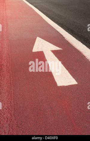 Weiß geradeaus ein Weg Richtung Pfeil Fahrbahnmarkierungen auf rotem Untergrund gemalt, Großbritannien - Stockfoto