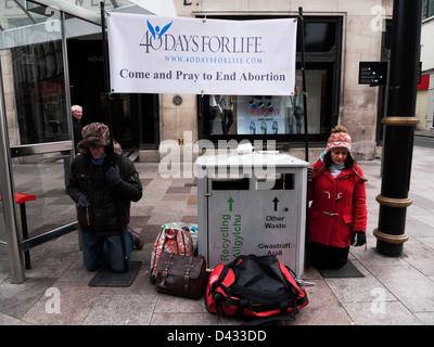 Anti-Abtreibung banner pro Leben Demonstranten auf Knien mit 40 Tage für das Leben beten St. Mary Street Cardiff - Stockfoto