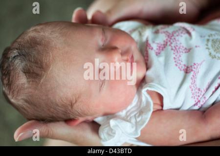 schlafende Säugling neugeborenes Mädchen statt von einer Frau - Stockfoto