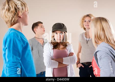 Porträt von Teenager-Mädchen in die Kamera, stehend in der Mitte der Gruppe der Teenager-Jungen und Mädels tragen Baseball Mütze suchen Stockfoto