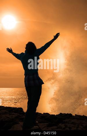 eine einsame Frau, hob die Arme in Ehrfurcht vor den mächtigen Wellen am Rande der Klippen in County Clare Irland - Stockfoto