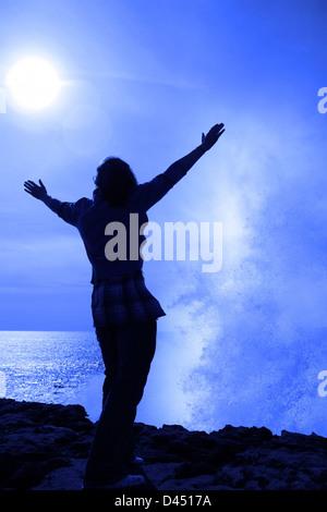 eine einsame Frau, hob die Arme in Ehrfurcht vor der mächtige Welle am Rande der Klippen in County Clare Irland - Stockfoto