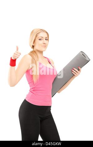 Fitness-Frau hält eine Ausübung Matte und einen Daumen aufgeben, isoliert auf weißem Hintergrund - Stockfoto