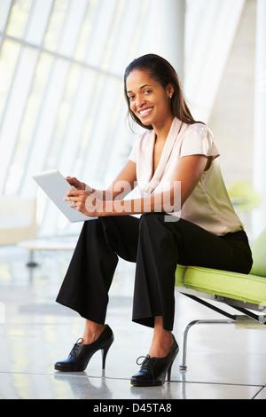 Geschäftsfrau, die sitzen In modernen Büros mit Digital-Tablette - Stockfoto