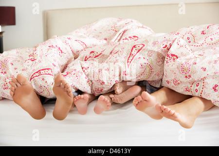 Familie Füße aus der Bettdecke im Bett stossen - Stockfoto