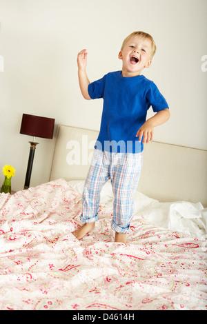Kleiner Junge Prellen auf Bett - Stockfoto