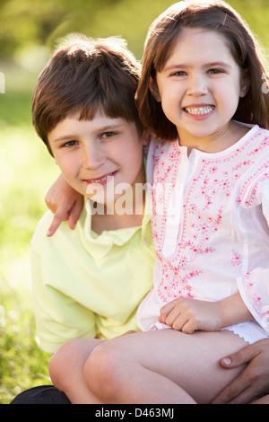 2 Kinder geben einander umarmen In Sommerwiese - Stockfoto