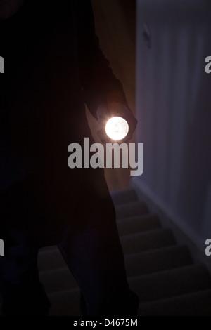 Schattenhafte männlichen Eindringling hält eine Taschenlampe oder Blitzlicht - Stockfoto