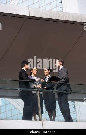 Vier Kollegen mit Diskussion außen Bürogebäude - Stockfoto