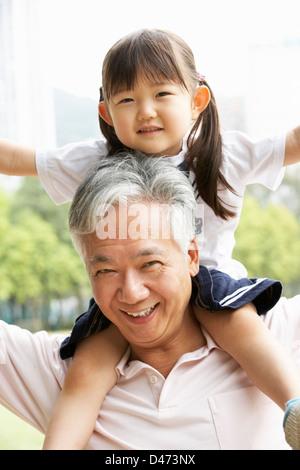 Chinesisch-Großvater geben Enkelin Fahrt auf Schultern im Park - Stockfoto