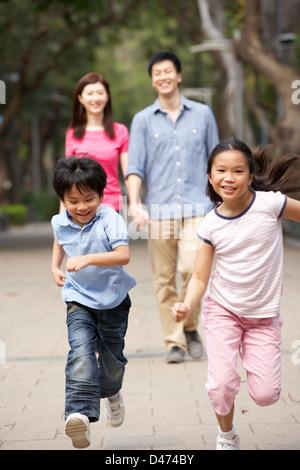 Chinesische Familie zu Fuß durch den Park mit fließendem Kinder - Stockfoto