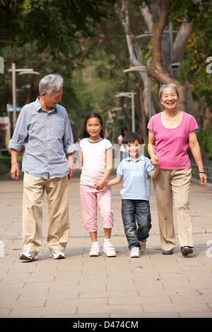 Chinesische Großeltern zu Fuß durch den Park mit Enkeln - Stockfoto