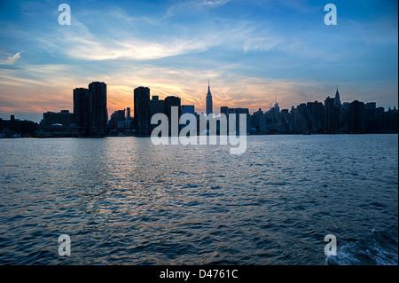 Silhouette Skyline von New York mit dem Empire State & Chrysler Building über East River nach Sonnenuntergang. - Stockfoto