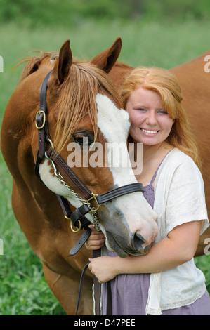 Lächelndes Mädchen mit ihrem Pferd im Portrait, Kopf geschossen rote behaarte Teenager und ihr Tier. - Stockfoto