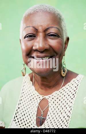 Alte schwarze Frau Porträt, Dame in eleganter Kleidung lächelnd auf grünem Hintergrund - Stockfoto