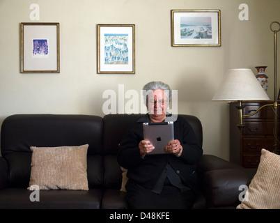 Reife Frau mit dem iPad zu Hause sitzen auf dem sofa - Stockfoto