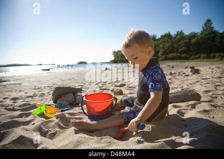 Kind spielt mit Sand am Strand - Stockfoto