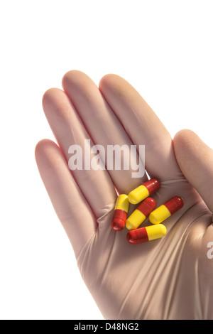 Behandschuhte Hand, die Tabletten in palm - Stockfoto