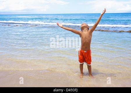 Ein kleiner Junge steht im seichten Wasser des Ozeans mit erhobenen Armen und nachschlagen; Hawaii Vereinigte Staaten - Stockfoto